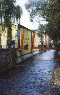 """Budynek fabryki włókienniczej nad rzeką, obecnie dom handlowy """"Wokulski"""""""