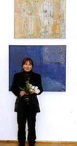 Elżbieta Kuraj na tle własnych prac w Galerii Uniwersyteckiej